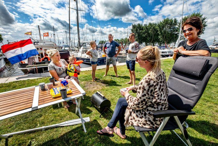 Vrouwen genieten in de zon op het terras aan het water in de passantenhaven van Heeg aan het Heegermeer. Beeld Foto Raymond Rutting / de Volkskrant