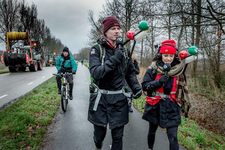 DJ's Sander Hoogendoorn en Eva Koreman lopen voor de vernieuwde 3FM-actie vanaf Den Oever naar Wieringerwerf, begeleid door tractors uit dorpsinitiatief.  Beeld Jean-Pierre Jans