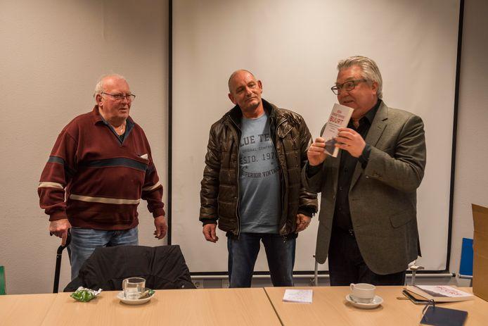 Hoogleraar Pieter Tops (rechts) showt zijn boek over de Tilburgse Vogeltjesbuurt aan de buurtbewoners Jo Janssens (links) en Jan de Fyter.