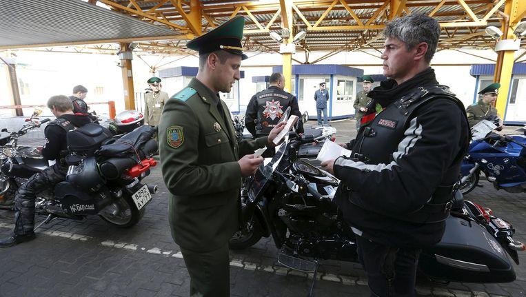 Een lid van de Nachtwolven toont zijn legitimatie aan een Wit-Russische grenswacht.