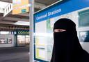 Moslima met nikab bij bushalte.