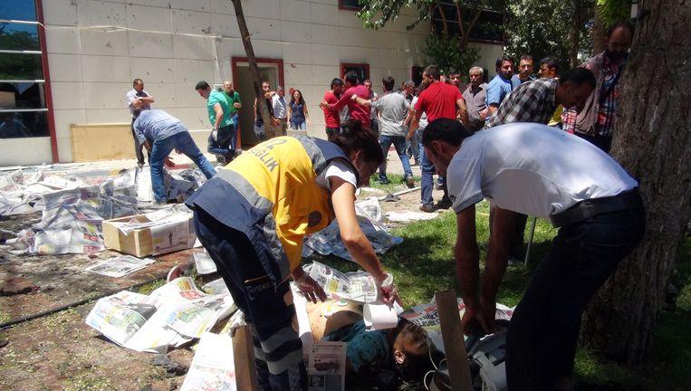 Lichamen worden afgedekt met kranten op de plek van de aanslag in Suruç. Beeld ap