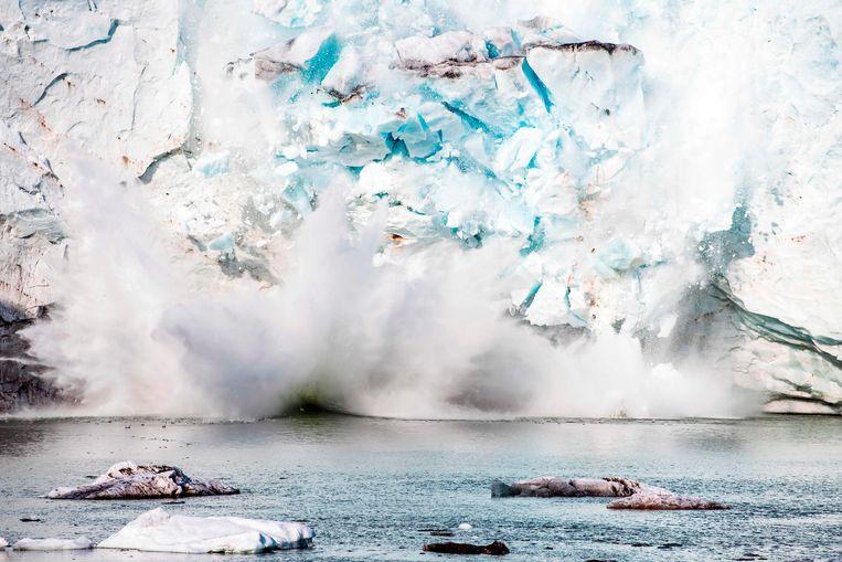 Een stuk ijs breekt af van de Apusiajik-gletsjer in Groenland. Beeld AFP