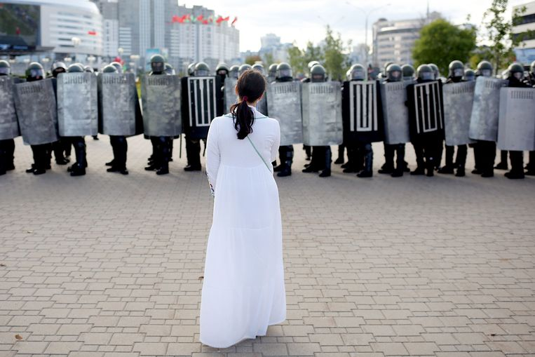 Een demonstrant staat voor de oproeppolitie tijdens protesten in Minsk. Beeld AFP