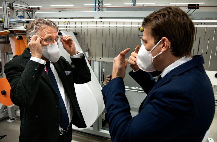 John Jorritsma (links) beproeft het medische mondkapje van VDL.  Willem van der Leegte geeft uitleg.