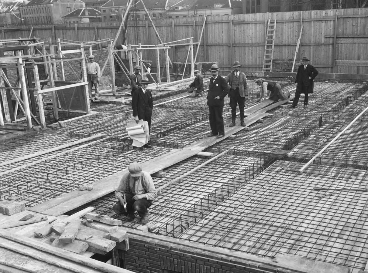 De architect Willem Diehl (centraal op de loopplank) en zijn assistent J.C. Spreij (met tekeningen) tijdens de bouw van het kantoor van de verzekeringsmaatschappij Vesta aan de Jansbuitensingel in Arnhem aan het begin van de jaren dertig van vorige eeuw.