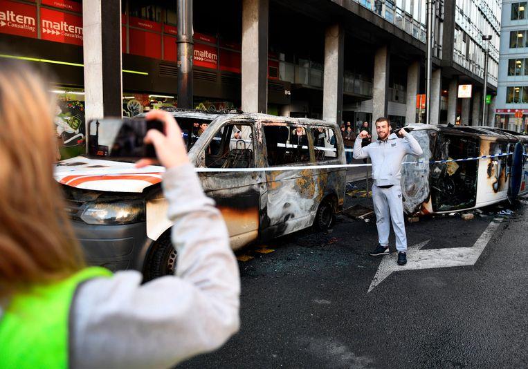 Een betoger poseert aan twee uitgebrande politievoertuigen.