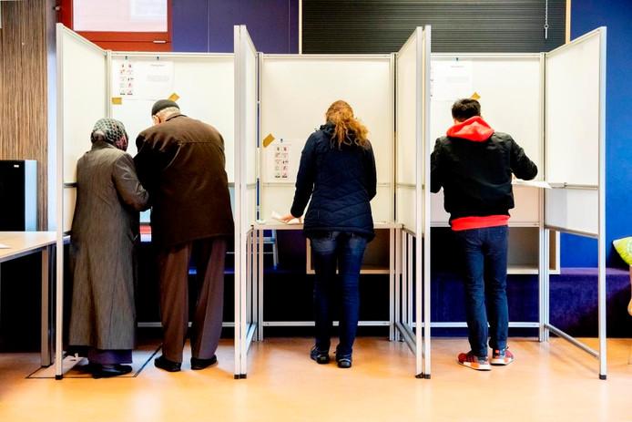 Man en vrouw stemmen samen in het stembureau aan de Trumanlaan in de Utrechtse wijk Kanaleneiland. Dat is verboden.
