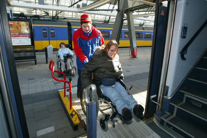 Een vrouw met beperking wordt door een NS-medewerker de trein in geholpen.