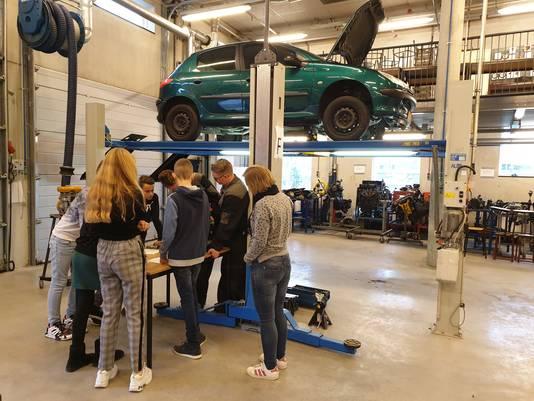 Derdejaarsstudenten in overalls geven uitleg aan de groep-achters hoe een automotor werkt.