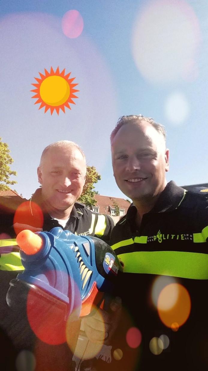De Renkumse wijkagenten Piet Enklaar (links) en Carlo Hoedt trekken met een waterpistool de wijk in.