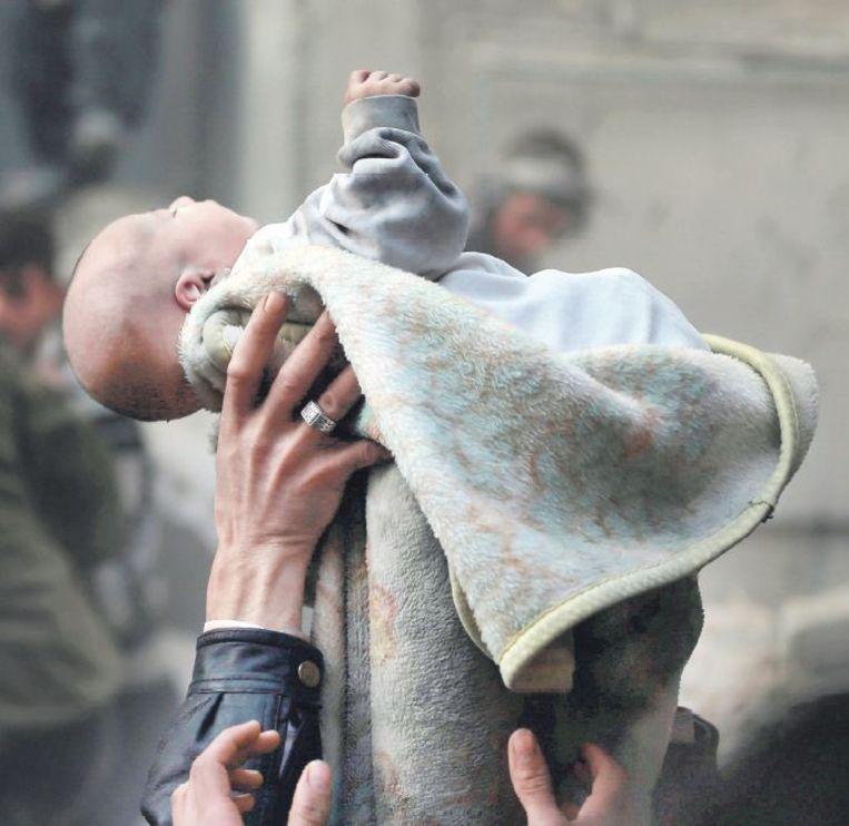 Damascus, 7 januari: mannen houden een baby omhoog. Het kind is gered uit het puin, na een luchtaanval door de Syrische luchtmacht. Beeld reuters