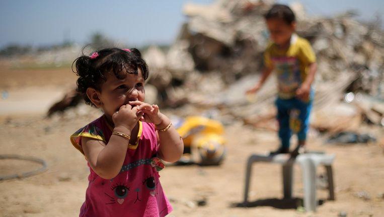 Palestijnse kinderen spelen voor gebouwen die in de zomer van 2014 verwoest werden.
