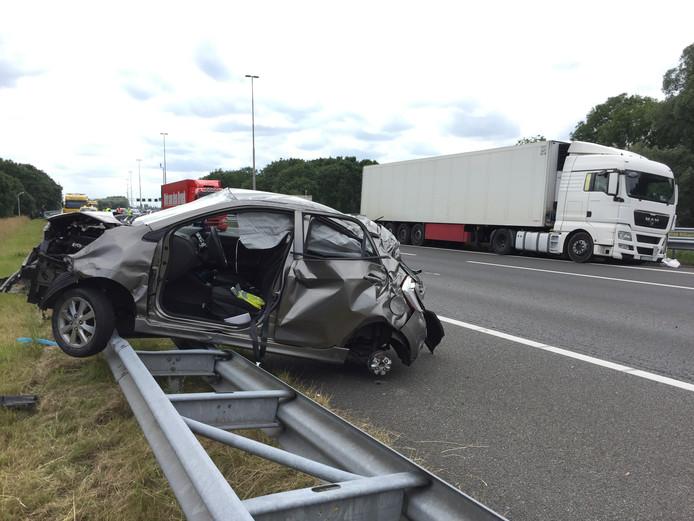 De geraakte personenauto staat op de vangrail.