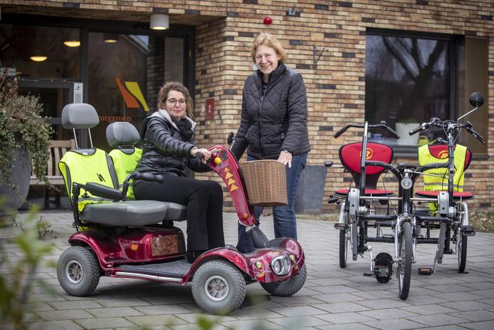 Mieke Bouwhuis (links) en Riet Westerbaan met de duoscootmobiel en de de tweezitsfiets.