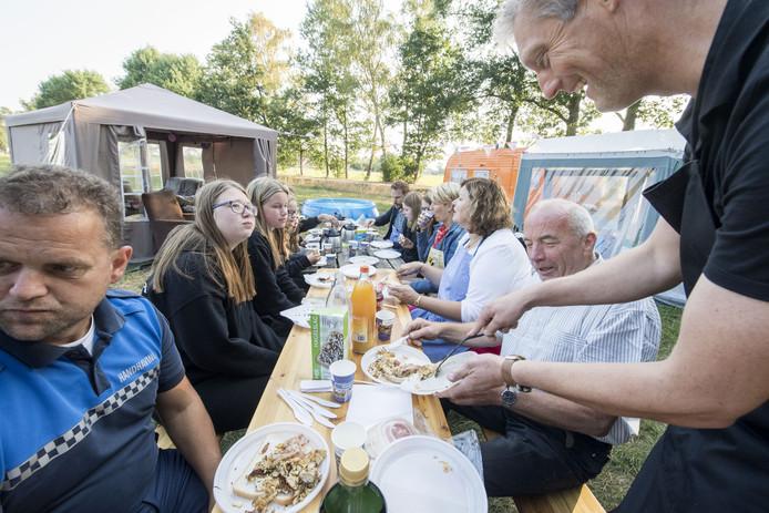 Wethouder Erik Volmerink (r) serveert ontbijt aan de jongeren die in Langeveen kamperen, links handhaver Nico Hesselink en rechts in het midden burgemeester Wilmien Haverkamp.