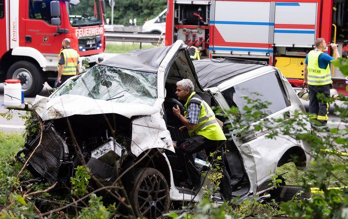 Duitse medewerkers van de politie doen onderzoek in het totaal vernielde busje.