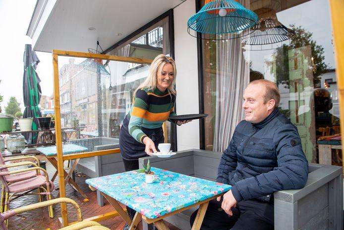 Daniëlle Schipper serveert bezoeker Mike Hoorn een kop koffie op het overdekte terras van Grand Café 't Dorp in Dedemsvaart. Het is nog de vraag of eigenares Alice Schipper na 1 november gebruikmaakt van het recht op een winterterras.