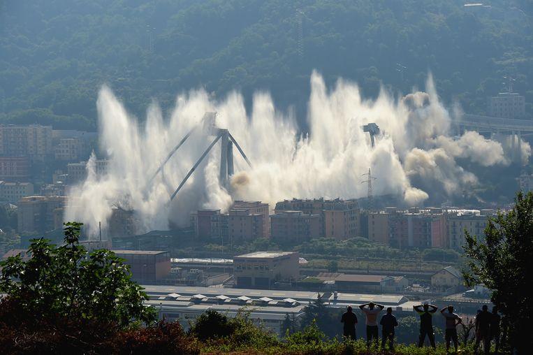 Circa tien maanden na het instorten van de snelwegbrug bij het Italiaanse Genua zijn de twee nog overeind staande pijlers opgeblazen. Op tv-beelden was vrijdag te zien hoe met explosieven een einde werd gemaakt aan de constructies van beton en staal, en hoe de pijlers in wolken stof verdwenen.  De Morandibrug stortte op 14 augustus vorig jaar in waardoor 43 mensen om het leven kwamen. Al maanden is gewerkt aan de sloop van de overgebleven rest van de brug. Inmiddels is ook begonnen aan de bouw van een nieuwe brug. Dat gebeurt onder leiding van de beroemde architect Renzo Piano die uit Genua komt. De nieuwe brug is naar verwachting in de loop van volgend voorjaar klaar. Beeld Getty Images
