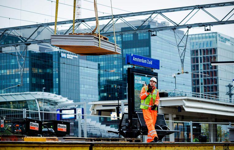De laatste werkzaamheden aan de A10 en het spoor bij station Amsterdam Zuid. Het project bij het station en de snelweg liep vertraging op waardoor een tijdige afronding in gevaar kwam.  Beeld ROBIN VAN LONKHUIJSEN/ANP
