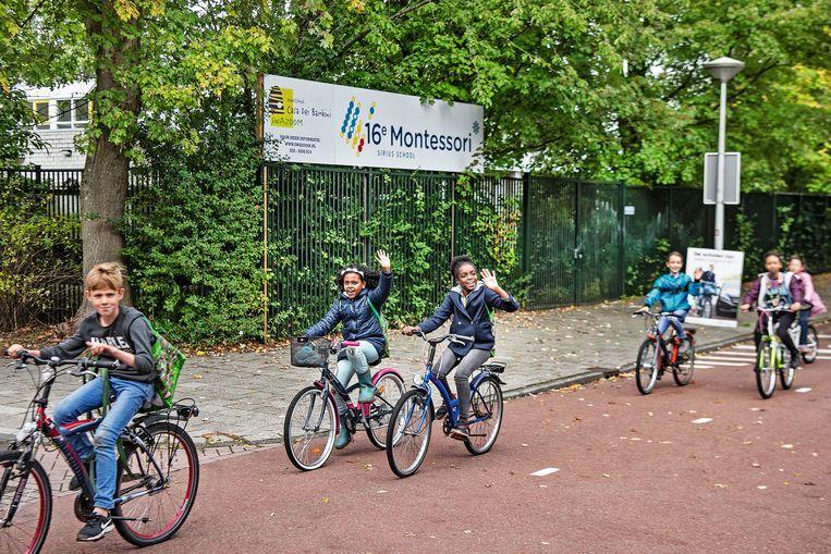 Een schoolklas passeert de 16e Montessorischool in Amsterdam Zuidoost. Beeld Guus Dubbelman
