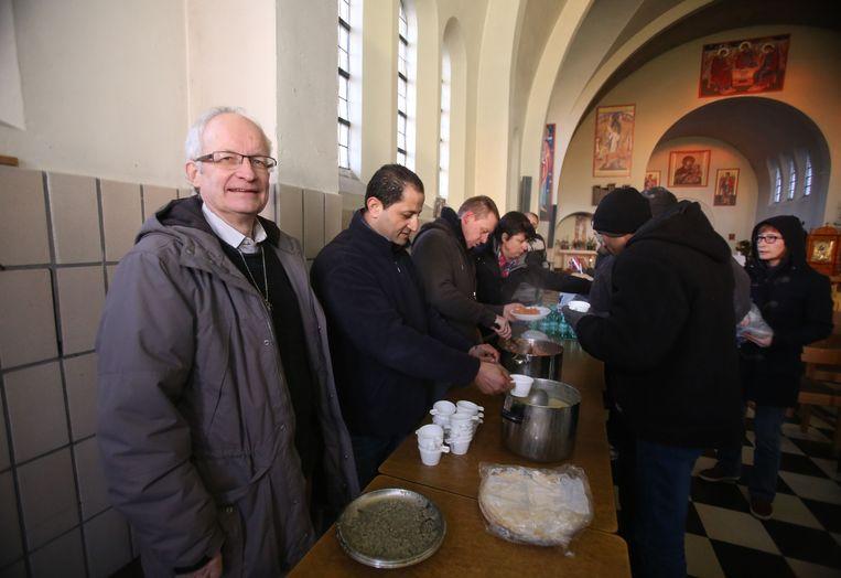 Zo was het vorige winter: pastoor Fernand Marechal (links) vangt vluchtelingen op in de Stella Mariskerk.