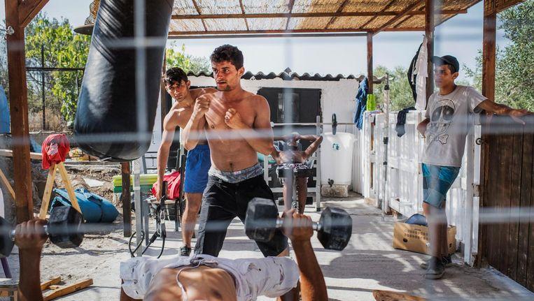 Migranten trainen in het 'One big happy family'-centrum in Moria. Er zijn overwegend jonge mannen in het kamp. Beeld Tycho Gregers / Jyllands Posten