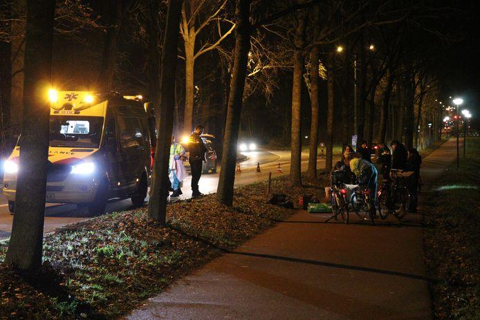 De fietser wordt behandeld door personeel van de ambulance.