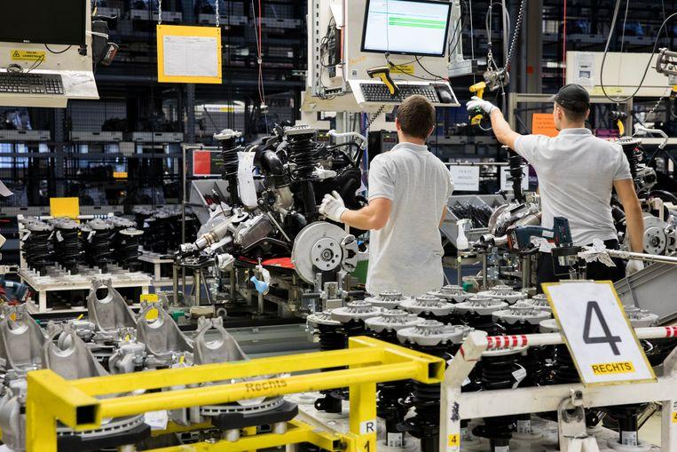 Medewerkers bij een assemblagelijn van Mini's bij autofabrikant VDL Nedcar in Born.  Beeld ANP