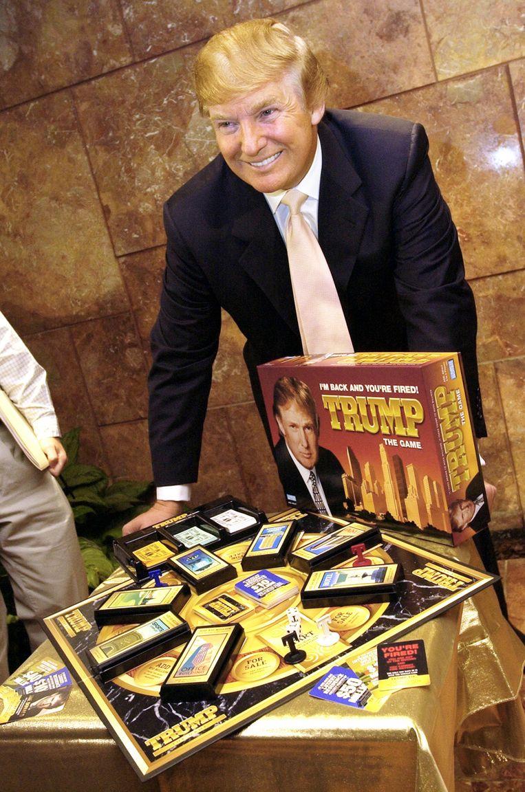 Donald Trump poseert in 2004 met een exemplaar van 'Trump: The Game', een soort monopolie waarbij spelers vastgoed kunnen kopen en verkopen voor miljarden dollars aan speelgoedgeld.
