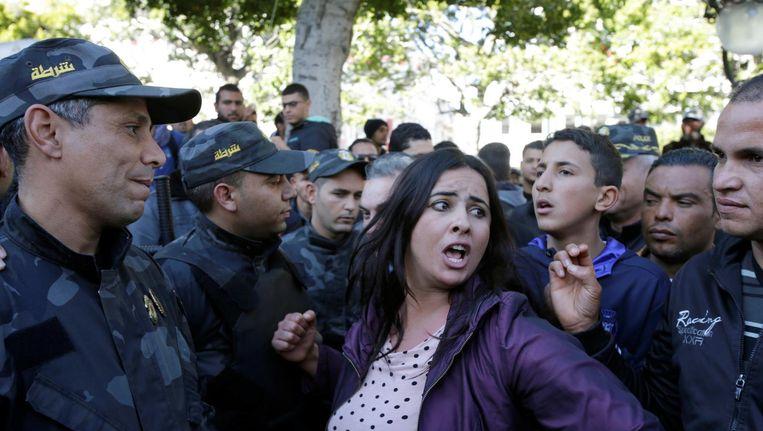 Demonstranten staan zondag in Tunis tegenover de oproerpolitie. Beeld reuters
