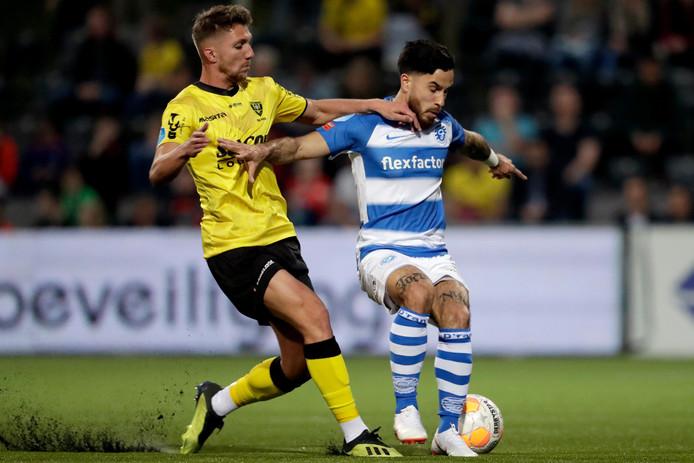 De Graafschap-verdediger Jordy Tutuarima schermt de bal af in een duel met VVV-aanvaller Peter van Ooijen.