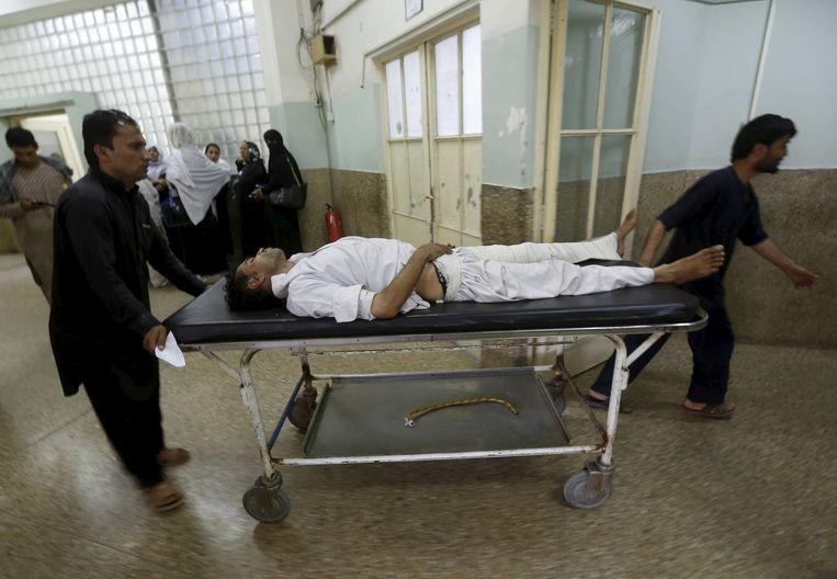Een slachtoffer van de aanslag nabij het vliegveld in Kabul wordt een ziekenhuis binnengebracht. Beeld reuters
