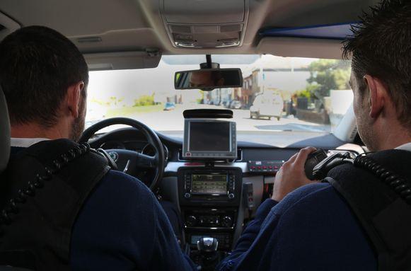 Agenten zitten in hun dienstwagen met flitsapparatuur.