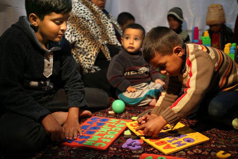 Syrische vluchtelingen krijgen Engelse les in een tent, die als geïmproviseerde school fungeert in een vluchtelingenkamp in Libanon. Beeld ap
