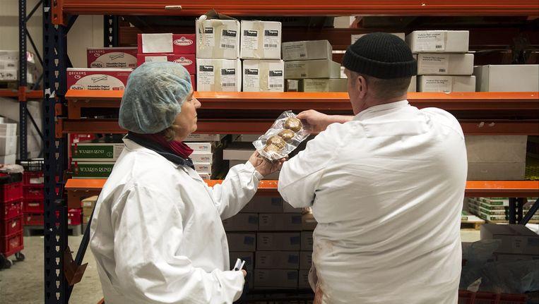 Een inspecteur (L) van de Nederlandse Voedsel- en Warenautoriteit (NVWA) controleert de gehaktballen van een Utrechts vleesverwerkend bedrijf op archiefbeeld. Beeld anp