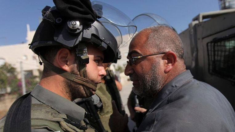 In Hebron op de West Bank komt een Palestijnse man verhaal halen bij een Israelische militair. Kort daarvoor had het leger een bron van de Palestijnen vernietigde. Beeld EPA