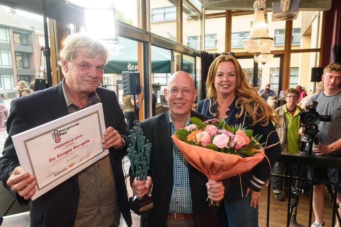 De uitreiking van de Persprijs aan De Slinger met de verslaggevers Gerard Smink (links) en Esther Rouwenhorst van deze krant.