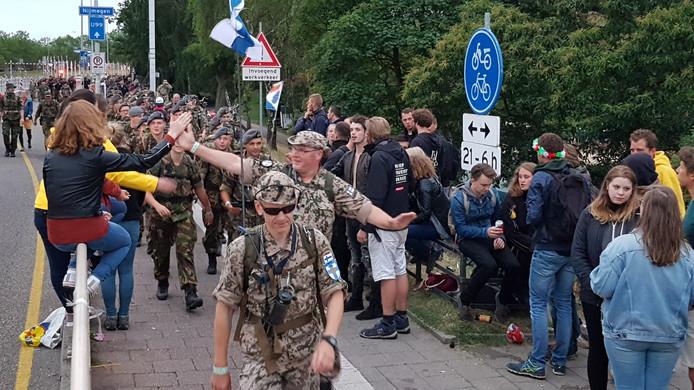 Net voor de Waalbrug staan jongeren de lopers nog aan te moedigen.