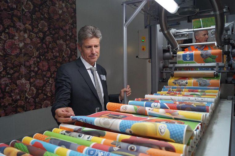 Grandeco CEO Patrick Molemans bekijkt het pas geprinte Paw Patrol-behangpapier.