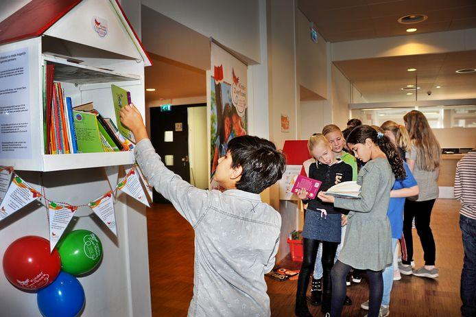 Kinderen bekijken de boeken in het Kinderzwerfboekstation in de Stadswinkel van het Stadskantoor in Dordrecht.