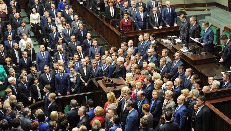 Oppositieleden keren parlementsvoorzitter Marek Kuchcinski (tweede van rechts achter het spreekgestoelte) de rug toe, terwijl deze het nieuwe parlementsjaar opent. Beeld AP