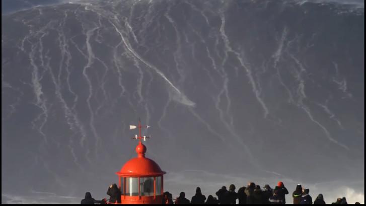 Surfer blijft overeind op megagolf in Portugal
