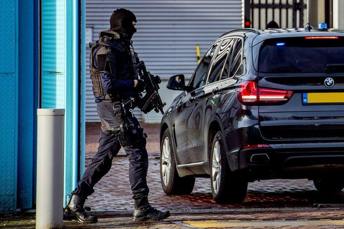 Zwaar bewapende agenten voor de ingang van de Extra Beveiligde Inrichting (EBI) Vught, waar met zwaailichten iemand naar binnen wordt gebracht.