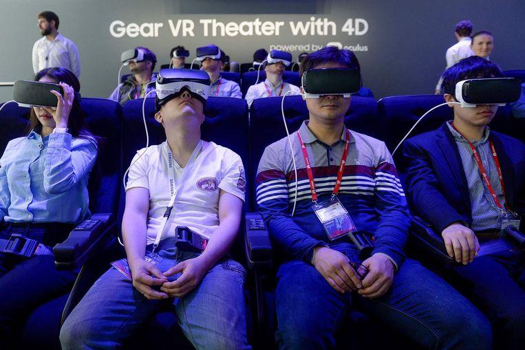Bezoekers van het MWC in Barcelona proberen de Gear VR-bril uit van Samsung. Beeld afp