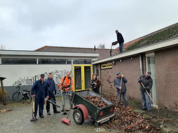Buurtbewoners ruimen het schoolplein in Markvelde op