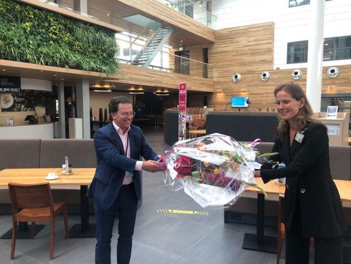 Directeur Petra de Kam van Veiligheidsregio Zuidoost-Brabant overhandigt bloemen aan bestuurder Frits van Hout van ASML als dank voor de hulp in verband met de coronacrisis.