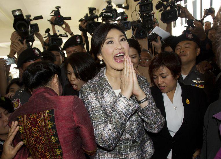 De Thaise voormalig premier Yingluck Shinawatra verlaat het parlement onder grote media-aandacht. Beeld ap