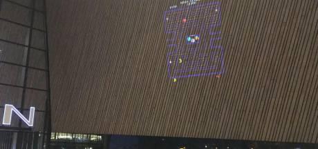Voorbijgangers spelen Pacman op gevel Rotterdam Centraal