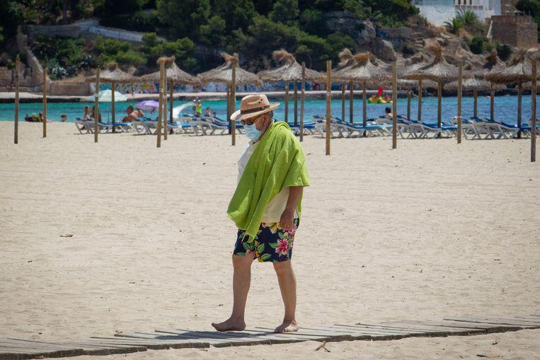 Een man met een mondkapje op een strand in Mallorca. Beeld AFP